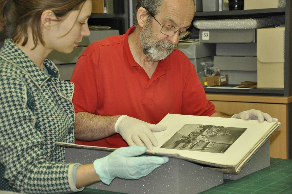 Lilian Coelho and Ian Moor examining a photographically illustrated printed book entitled 'Artists at Home' illustrated with Photogravures by J. P. Mayall printed in 1884.